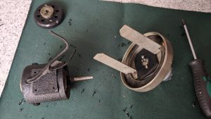 The old motor from the watch cleaning machine with the new one fastened to the circular base